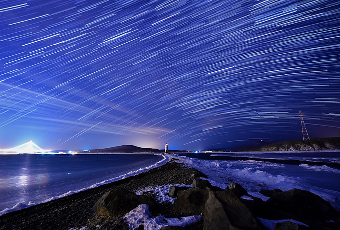 The Geminids meteor shower during its peak, in the night sky over Tokarevsky Lighthouse on Egersheld Cape, Russia, December 13