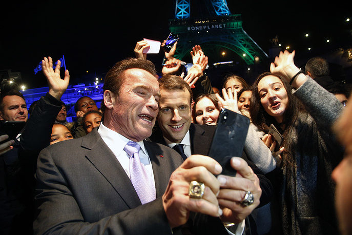 France's President Emmanuel Macron and Arnold Schwarzenegger take a selfie with young people in front of the Eiffel Tower illuminated in green, aboard a boat cruising on the Seine river back from the One Planet Summit, Paris, France, December 12