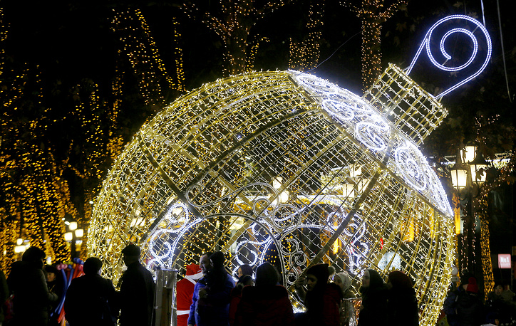 People walk past Christmas decorations and lights in the centre of Tbilisi, Georgia
