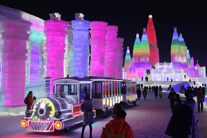People visit the ice sculptures illuminated by coloured lights at the opening of 34th Harbin International Ice and Snow Festival in Harbin city, China