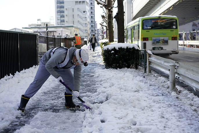 A worker clears snow from a sidewalk after snowfall in Tokyo