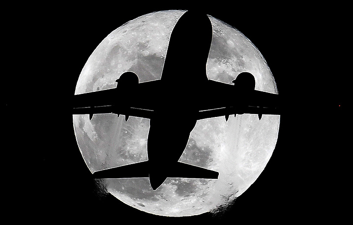 A plane is silhouetted against a supermoon, seen from London, Britain