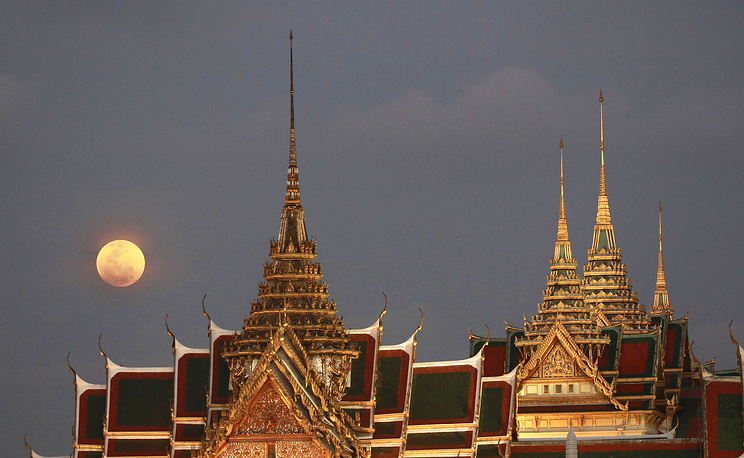 A full moon rises behind the Grand Palace in Bangkok, Thailand
