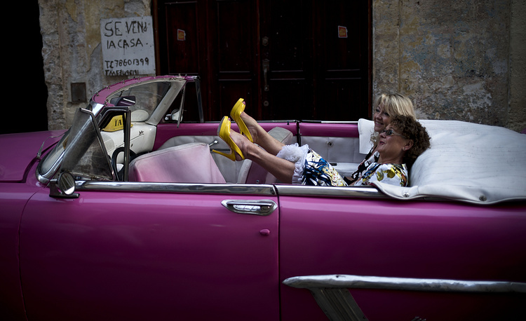 A tourist kicks up her heels as she and a friend wait for the driver of a hot pink private taxi, a classic American Chevrolet convertible, before they take a driving tour of Havana, Cuba, January 31