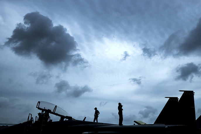 Republic of Singapore Air Force staff are silhouetted as they stand atop an F-15SG fighter jet