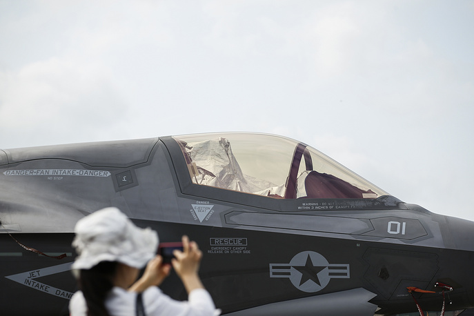 A visitor takes a photo of an F-35B fighter jet