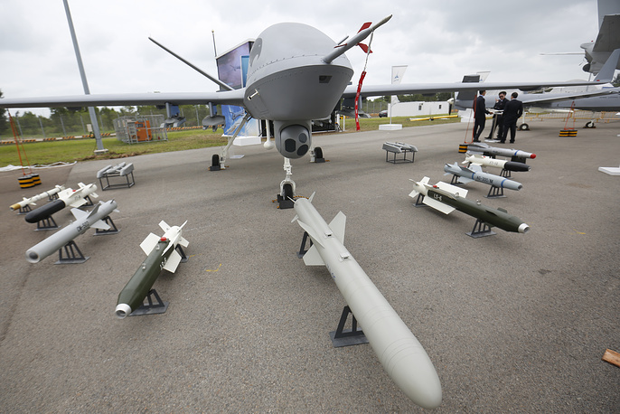 Mock weapons are laid out around a China National Aero-Technology Import & Export Corporation (CATIC) Wing Loong II Unmanned Aerial Vehicle (UAV)