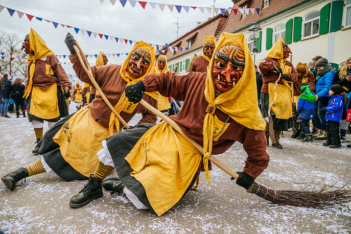 Revelers decked out in traditional colorful costumes and painted, wooden masks participate in the annual Fasnacht carnival parade in Oberdischingen, Germany, February 4