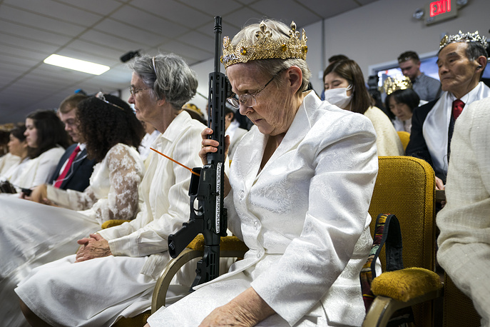 A parishioner with the Sanctuary Church holds onto her AR-15, which churchgoers were encouraged to bring to a blessing ceremony to rededicate their marriages at the World Peace and Unification Sanctuary in Newfoundland USA, February 28