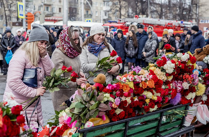 People lay flowers for the victims of a fire in Kemerovo