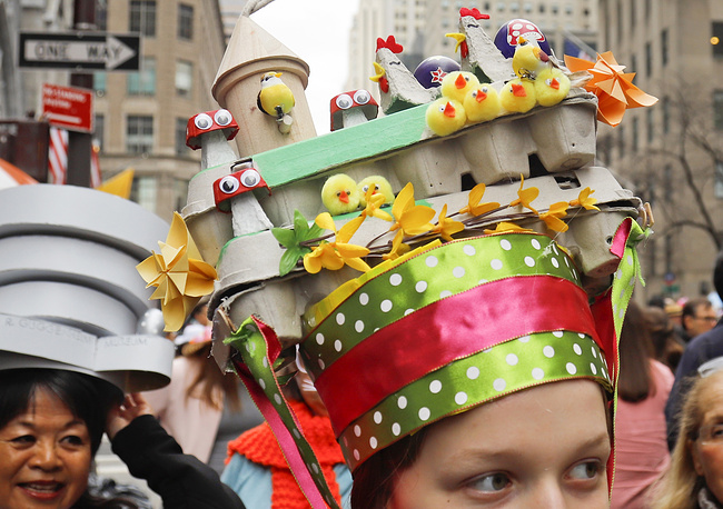 A woman wears a hat crafted from items in her house included egg cartons, during Easter celebrations in New York