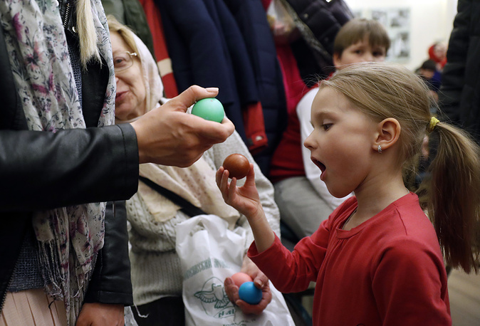 A young girl receives an Easter egg after Easter church service in Moscow