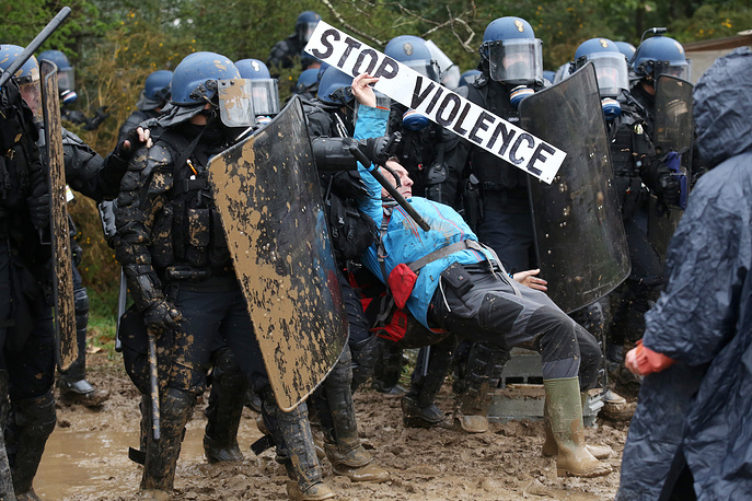 A protester holding a sign 'Stop Violence' is arrested by French police during their operation of evicting environmental protesters from the ZAD 'Zone A Defendre' (Zone to defend) area in Notre-Dame-des-Landes, north of Nantes, France, April 9