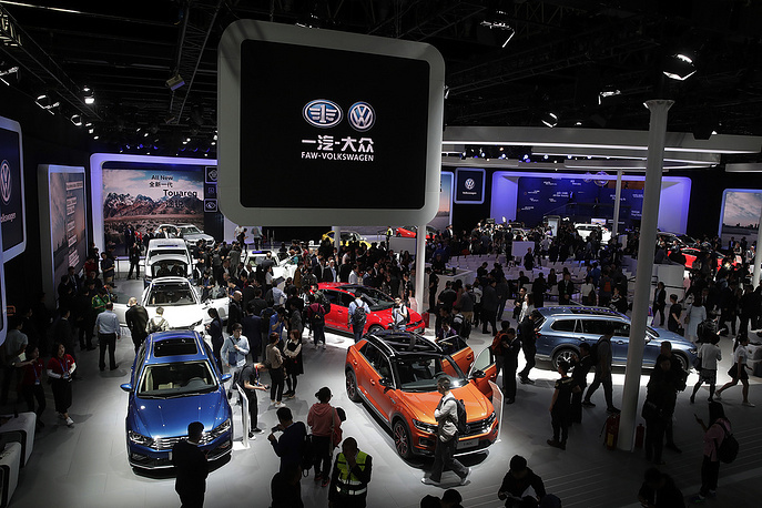Journalists and visitors look at the Volkswagen car models