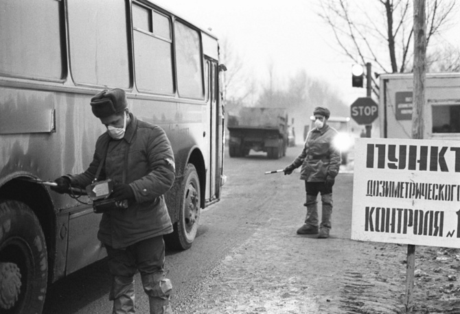 Worker of a Radiation Control Post monitors radiation level of a bus, leaving the Chernobyl Exclusion Zone, 1987