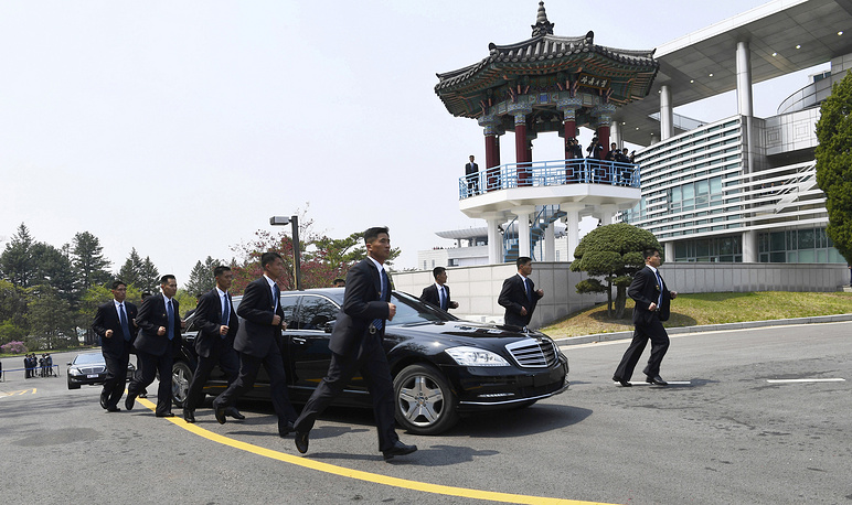 North Korean security persons run by a car carrying North Korean leader Kim Jong Un return to the North side for a lunch break after a morning session of a summit meeting with South Korean President Moon Jae-in