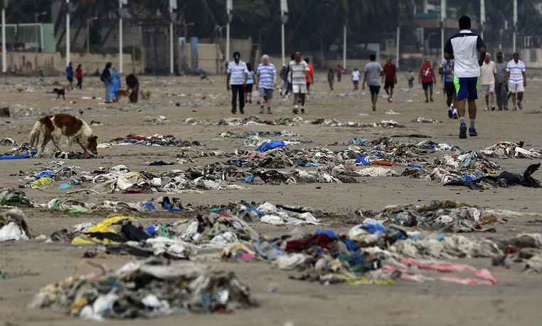 People walk on the garbage littered shores of the Arabian Sea in Mumbai, India