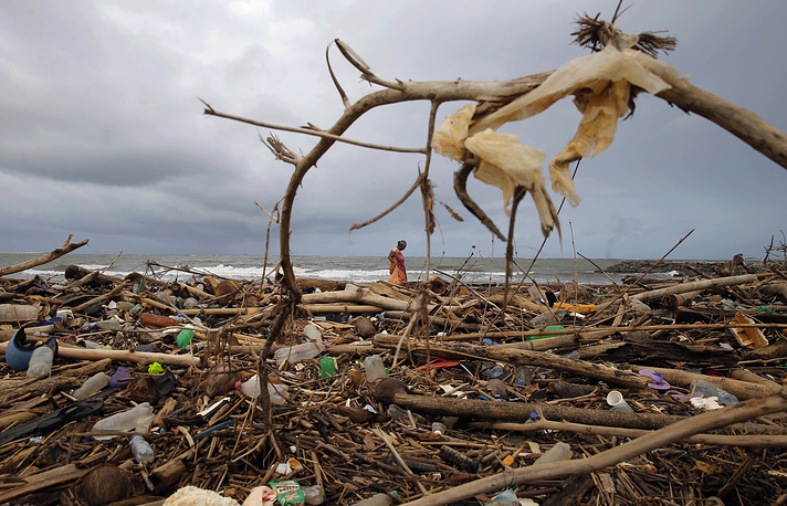A Sri Lankan ragpicker searches for plastic waste washed ashore on the promenade of the Indian ocean in Colombo, Sri Lanka