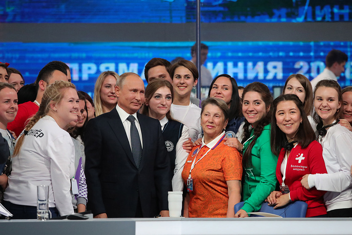 Russia's President Vladimir Putin poses for a group photo with volunteers after his annual Q&A session
