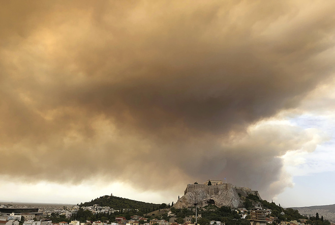 A plume of smoke turning large parts of the sky orange, with the ancient Acropolis hill at centre