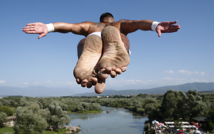 Spectators watch as diver Florid Gashi, winner of the competition, performs the winning jump from the Ura e Fshejte bridge during the 68th traditional annual high diving competition, near the town of Gjakova, Kosovo, July 22