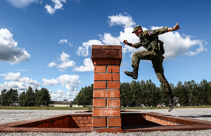 A participant from Russia competes in a relay race incorporating an obstacle course for air assault units with small arms during the Airborne Platoon contest