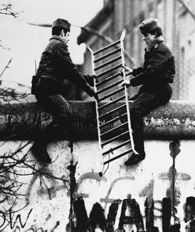 East German border guards take a ladder back over the wall to East Berlin after correcting the border line between the West Berlin district of Wedding in the French sector and Prenzlau in East Berlin, 1989