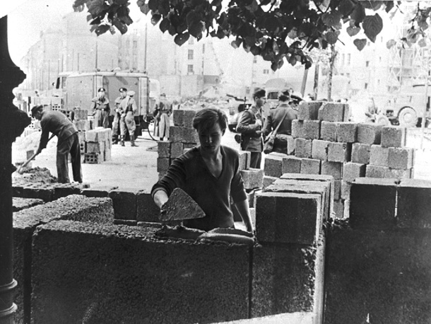 An East German worker lays some of the first stone blocks of the Berlin Wall, shortly after the border between East and West Berlin was sealed, 1961