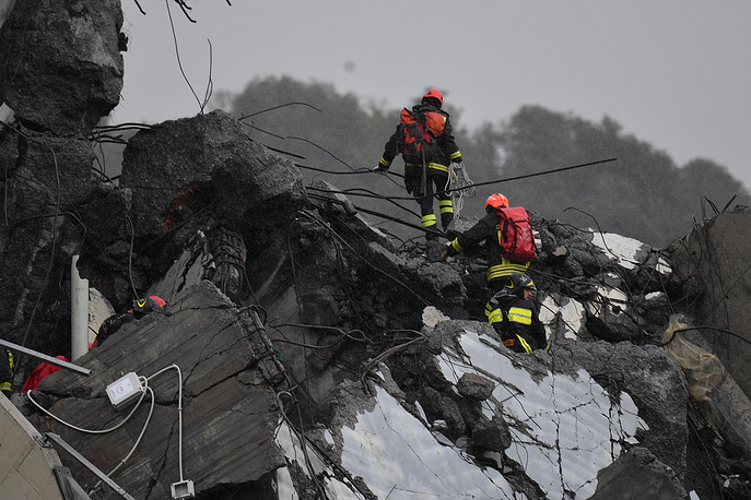 Rescuers at the site of the collapsed bridge in Genoa