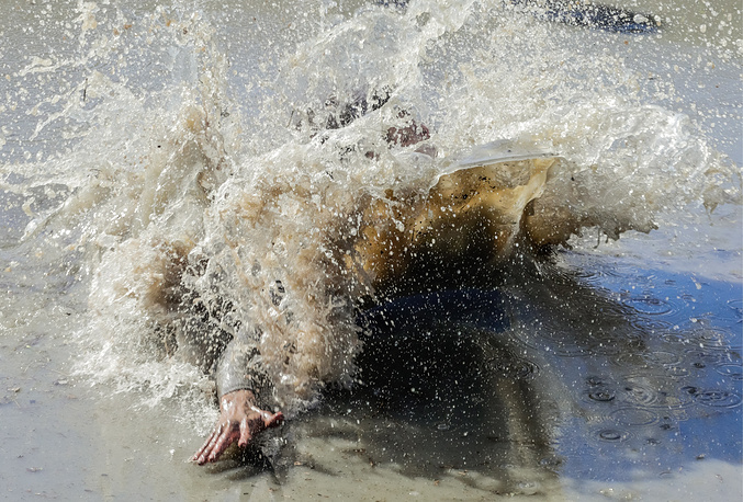 A man swims in muddy water as he competes in the Race of Heroes obstacle course race superfinal at the Sorochany ski resort near Moscow, September 15