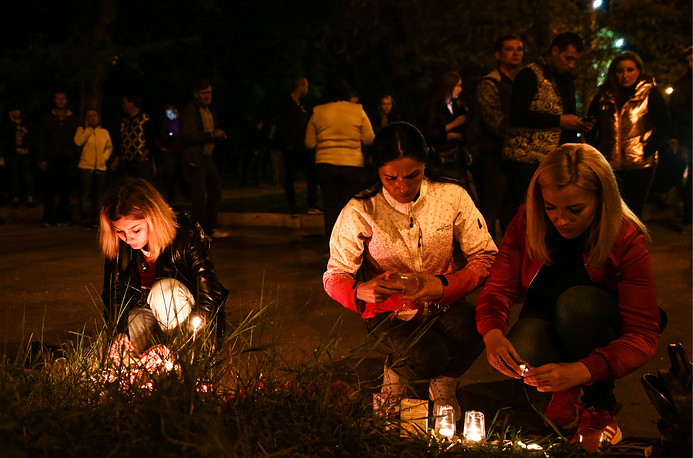 People lighting candles near the building of the Kerch polytechnic school