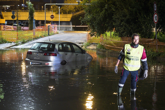An Italian policeman wades in a flooded street near an abandoned car, in Rome