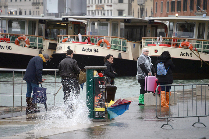 Tourists walk with their luggage in Venice