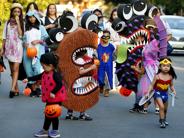 """Children, dressed in their colorful costumes make the rounds of the houses to solicit candies and sweets known as """"trick or treat"""" to celebrate Halloween in suburban Makati city, Philippines"""