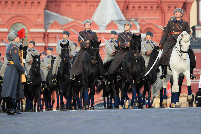 Russian servicemen dressed in historical uniform ride horses during the parade