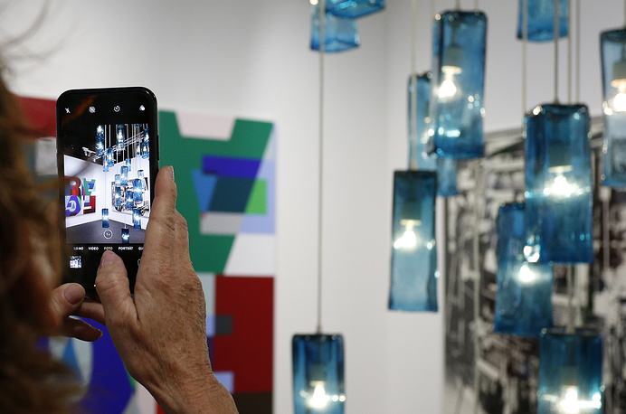 An Art Basel patron photographs a sculpture during in Miami