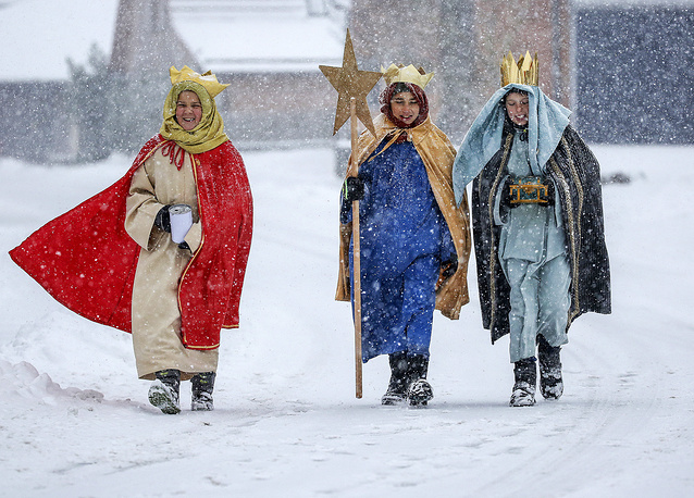 Coral singer in traditional costumes walk through the snow in Eglingen, southern Germany, January 5