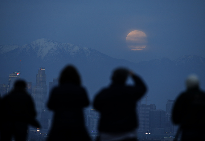 People watching the supermoon rise behind the downtown Los Angeles skyline, from Kenneth Hahn Park in Los Angeles