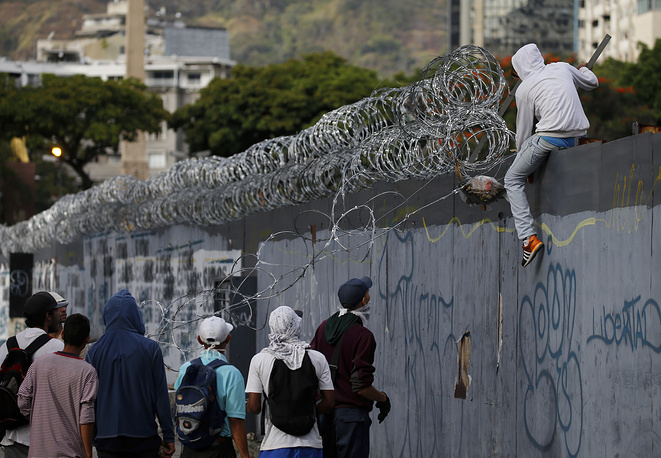 Anti-government protesters tear off razor wire from a wall during clashes in Caracas