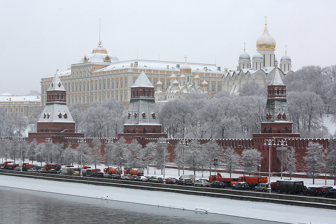 Cars and snow clearing equipment driving on Kremlyovskaya embankment in Moscow