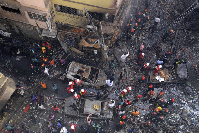 Rescuers stand at the site of the fire in Dhaka, Bangladesh