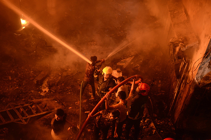Firefighters and local people help douse a fire