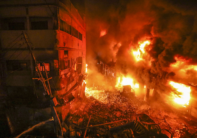 Flames rising from a fire in a densely packed shopping area in Dhaka