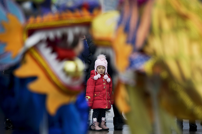 A child watches dragon dance performance during the Lantern Festival at a square in Yufa town of Beijing's Daxing district, February 19