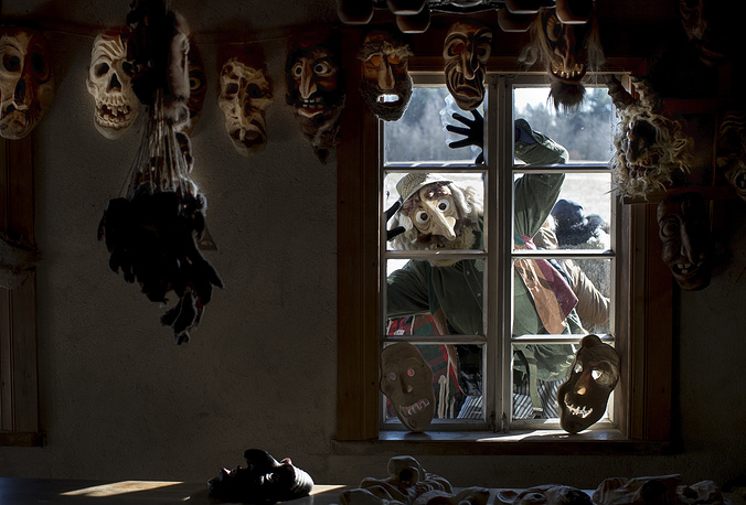 A performer wearing a traditional carnival mask looks through a window in Shrovetide celebrations, in Rumsiskes village, Lithuania