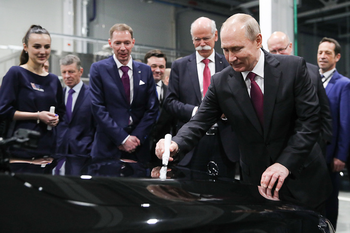 Russia's President Vladimir Putin leaving a signature on a Mercedes-Benz car assembled at the 'Moskovia' Mercedes-Benz assembly plant, Moscow Region, April 3