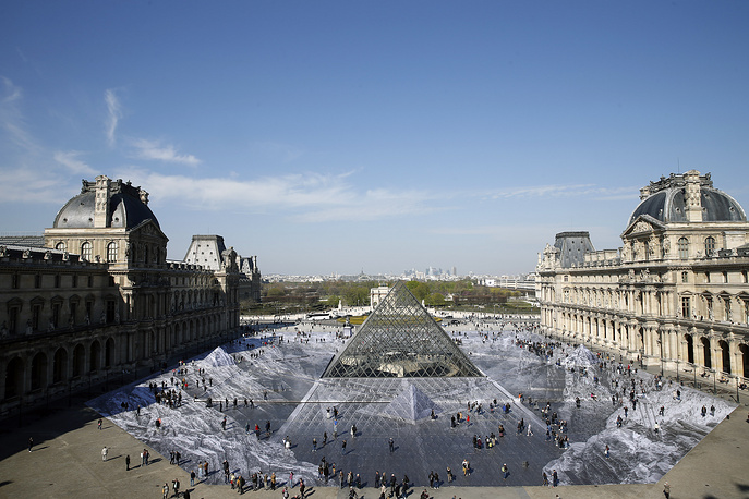 Tourists walking on a giant photographic work by French photographer and artist Jean Rene, known as JR in the main courtyard Cour Napoleon of the Louvre Museum in Paris, March 30