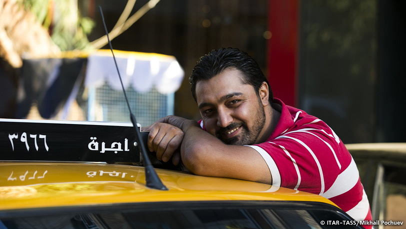 September 19. Taxi driver takes a break leaning on his car.