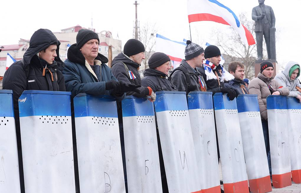 A self defense unit in Crimea carries shields with the colours of the Crimean flag  ITAR-TASS/Valery Matytsin