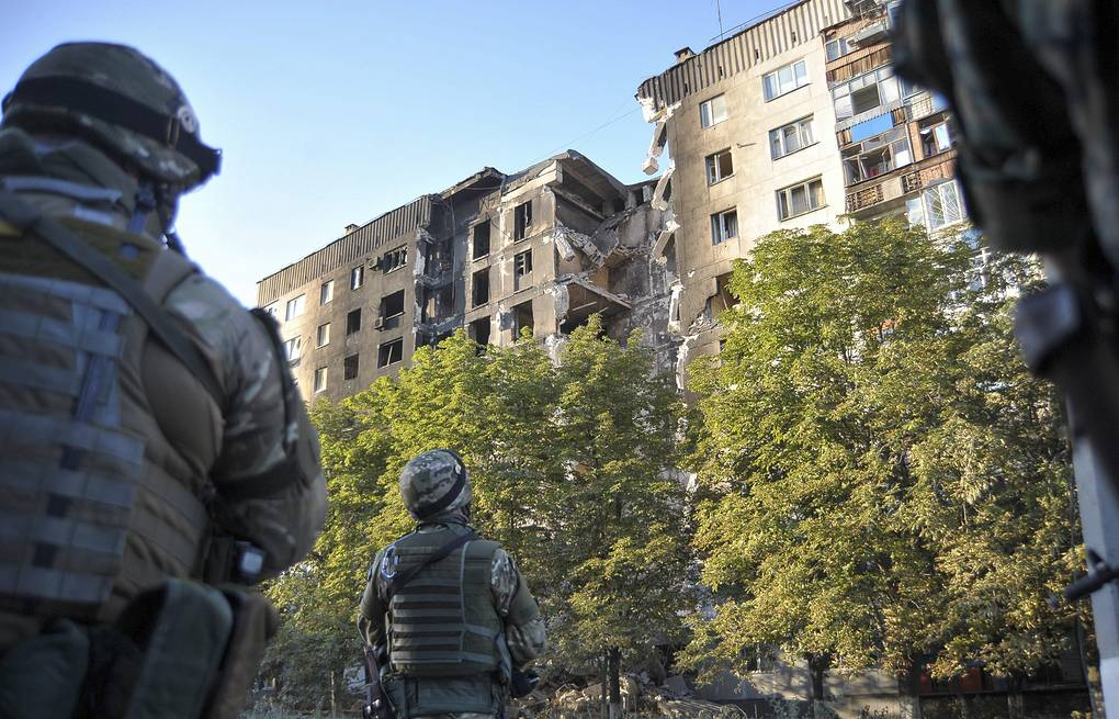 Ukrainian soldiers look at the damage sustained to a building in Lisichansk  EPA/IVAN BOBERSKYY
